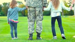 Two daughters of a soldier. Close up back view military father with kids standing together.