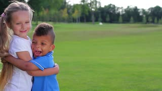Two kids are standing on the glade, hugging each other and laughing.