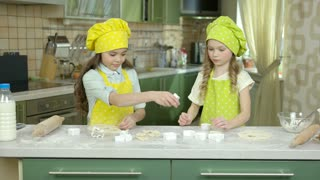 Two little girls cooking. Kids in chef uniforms. Sisters making a cake.