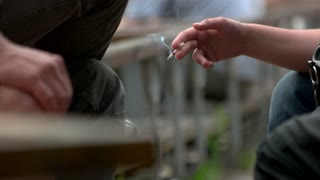 Two smoking people. Male and female hands with cigarettes, close up.