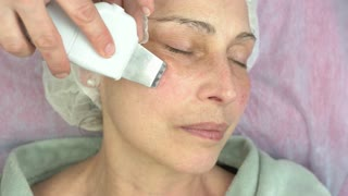 Ultrasonic face cleaning procedure. Work of cosmetician, mature woman. Slowing down skin aging.