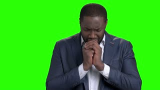 Unhappy businessman is crying on green screen. Depressed afro american entrepreneur on Alpha Channel background. Regrretting about something. Young dark-skinned man is praying.