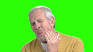 Unhappy elderly man having toothache. Senior man in casual wear suffering from toothache, chroma key background.