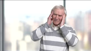 Unhappy senior man suffering from headache. Stressed elderly person having pain in his temples.