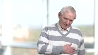 Unhappy senior massaging his chest. Older man holds his chest as he suffers from a heart attack, blurred background. Symptoms of heart problems.