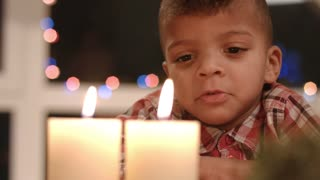 Upset child looking at candle. Sad boy beside Christmas candles. Feeling sad on Christmas night. Christmas midnight at home.