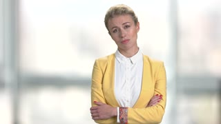 Upset woman with arms crossed. Bored displeased business lady on blurred background. Fatigue from waiting.