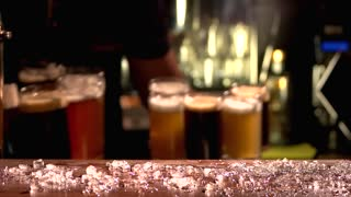 Variety of colourful beers place on table. Barman putting beer mugs of different colours on the table with ice cubes, slow-mo.