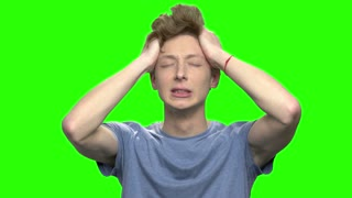 Very angry stressed young boy screaming. Nervous breakdown. Green screen hromakey background for keying.