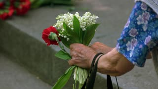 Very old lady with flowers at memorial day. Close up. Hands of senior grandmother with flowers bouquet.