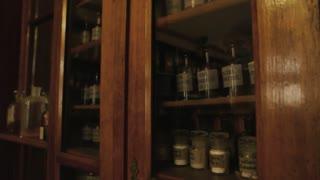 Vintage drugstore shelves. Old pharmaceutical bottles with labels. First medicine breakthroughs.