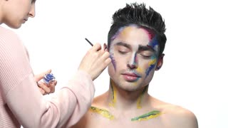 Visagist applying artistic makeup. Handsome caucasian male model.