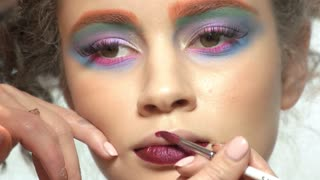 Visagist is using lipstick brush. Female model, colorful artistic makeup.