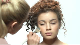Visagist with brush applying makeup. Pretty young model. Easy makeup tutorial for beginners.