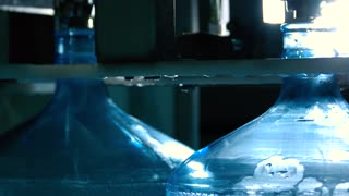 Water filling up bottles. Transparent liquid in motion. Best quality of purification. Five gallons of mineral water.