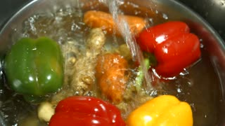 Water splashes on vegetables. Ginger root and bell pepper. Vegetarian food in restaurant kitchen. First step of cooking meal.