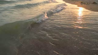 Waves on seashore, slow-mo. Sea during sunset.