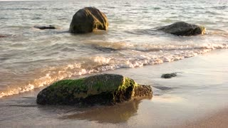 Waves, sand and stones. Sea in slow-mo.