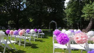 Wedding ceremony in the park. Wedding decorations. Chairs with colored bows.