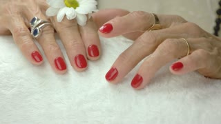 Well-groomed hands after spa therapy. Old woman wet hands with beautiful red manicure moving with fingers on white towel. Skin and hands care.