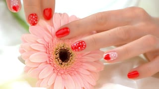 Well-groomed hands and flower, slow motion. Delicate female hands with beautiful romantic manicure gently caress gerbera flower on white silk. Femininity and sensuality concept.