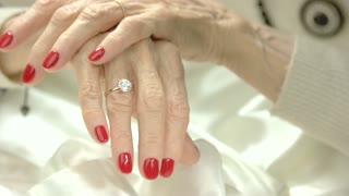 Well-groomed hands with jewelry. Caucasian senior woman hands with red manicure wearing expensive rings.