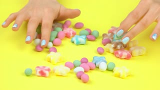 Well-groomed hands with winter manicure. Woman hands with beautiful winter manicure placing multicolored sweet candies on yellow background.