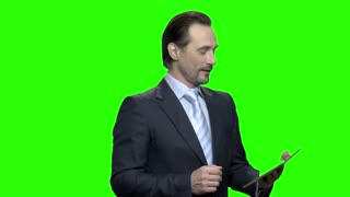 Well presented man with tablet talks to camera. Green hromakey background for keying.