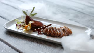 White plate with meat. Meat dish on wooden background. Duck breast and dry ice. Example of european cuisine.