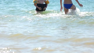 Woman and little girl bathe in the sea. Beach vacation. Summer is in full swing. Child with inflatable accessories.
