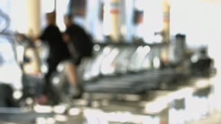 Woman and man burn calories on the exersice bikes. Blurred background of gym. Woman and man are working out in gym.