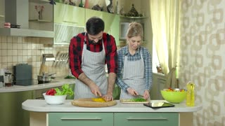 Woman and man cooking. Tablet on kitchen table.