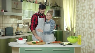 Woman and man eating apple. Young people in the kitchen. Dieting with your partner.