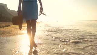 Woman carrying flip flops, seashore. Back view of walking lady.