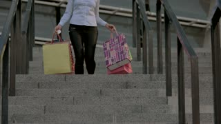 Woman carrying shopping bags. Lady walking downstairs. How to shop smart.