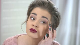 Woman checking her makeup. Beautiful caucasian girl. Romantic makeup tutorial.