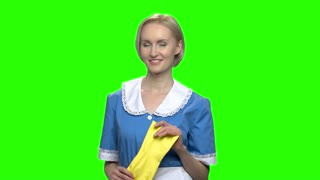Woman cleaner puts on rubber gloves. Green hromakey background for keying.
