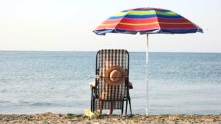 Woman enjoying morning sunbath near seashore. Rear view beach chaise longue and umbrella. Summer vacation and resort concept.