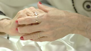 Woman fingers touching ring on her finger. Old woman well-groomed hands with luxury red manicure and diamond. Beauty and wealth concept.