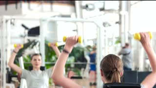Woman flexing hands with dumbbells. Young athletic woman training with weights at fitness center. How to build muscles for women.