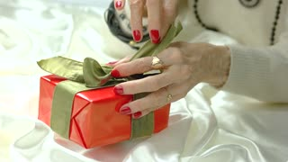 Woman hands untied bow on gift box. Well-groomed hands of aged woman with red manicure unpacking red gift box. Birthday gift concept.