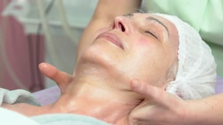 Woman having lymphatic face massage. Hands of masseuse, adult female. Lymph drainage techniques.