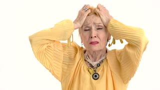 Woman holding head in desperation. Upset old lady isolated.