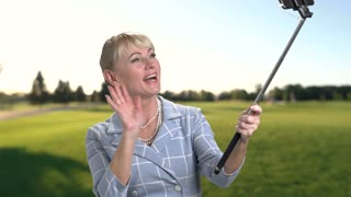 Woman holding monopod and waving with hand. Cheerful woman using selfie stick outdoors. Selfie on nature background.