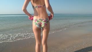 Woman in bikini dancing, slow-mo. Female body and horizon.