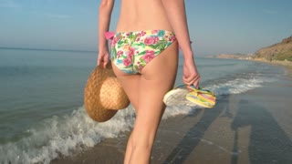 Woman in bikini walking, seashore. Slim female body.