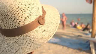Woman in hat, blurred seashore. Lady near sea. The summer vibes.