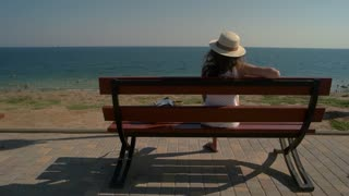 Woman on bench, sea background. Lady relaxing outdoors. Place to think.