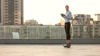 Woman on hoverboard, urban background. Businesswoman with tablet. World of possibilities.