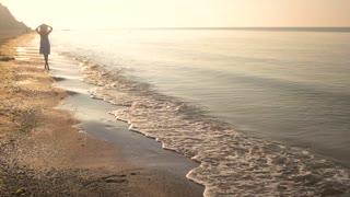 Woman on sunny seashore. Lady walking near water.